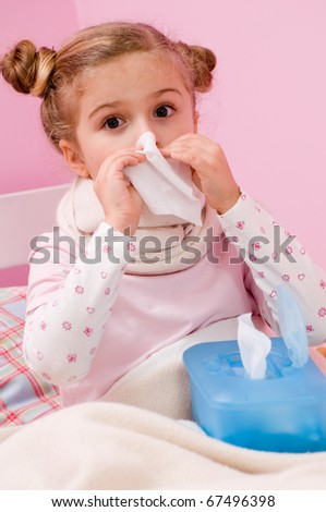Sick little girl blowing her nose - stock photo
