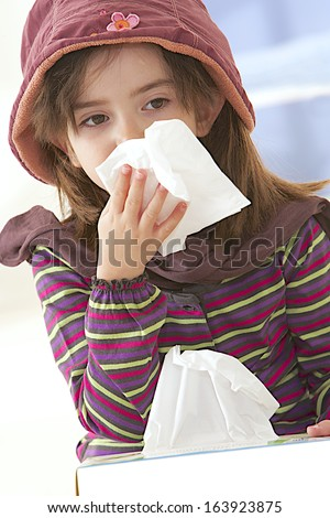 Sick little girl blows her nose, holding a tissue box - stock photo
