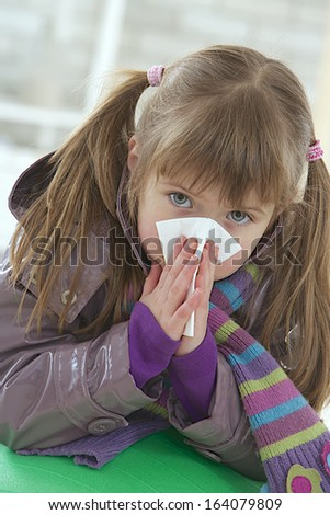 Sick little girl blows her nose, with a tissue  - stock photo