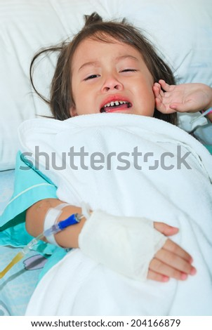 Sick little girl cry on hospital bed and hand with intravenous injection - stock photo