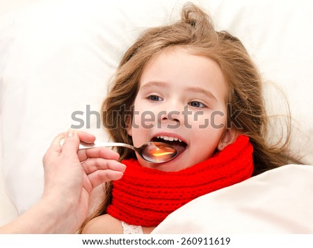 Sick little girl in bed taking medicine with spoon