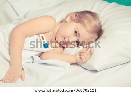 Sick little girl in bed.Virus, flu, cold, fever. - stock photo