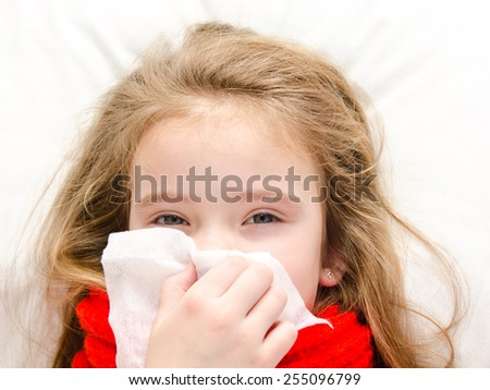 Sick little girl lying in the bed and blowing her nose - stock photo