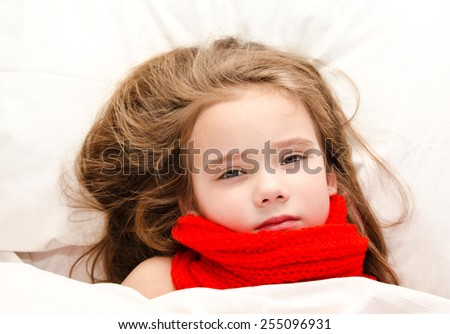 Sick little girl lying in the bed in red scarf - stock photo