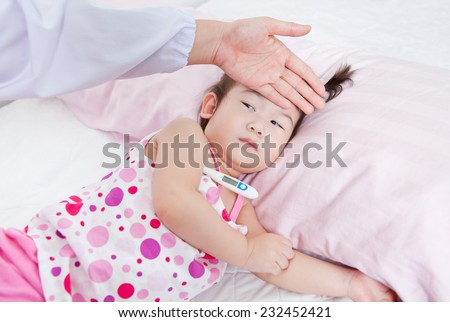 Sick little girl nursed by a pediatrician, doctor touching forehead little asian girl,girl lying with digital mercury thermometer - stock photo