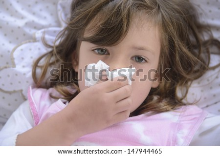 Sick little girl sneezing in bed - stock photo