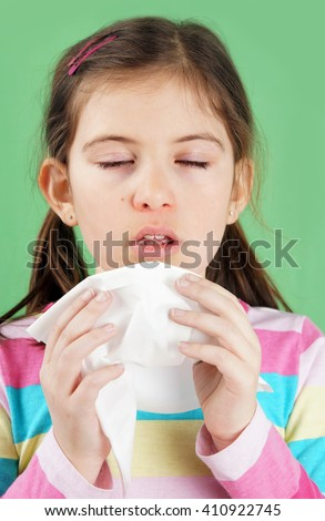 Sick little girl with cold about to sneeze in paper tissue - stock photo