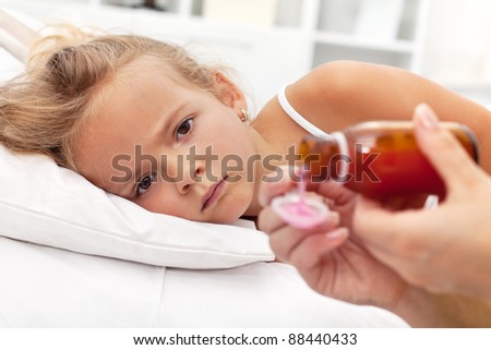 Sick little girl with flu awaiting medication- focus on the eyes