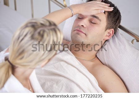 Sick man in bed, female doctor puts her hand on forehead - stock photo