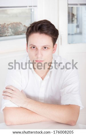 sick man in white shirt sitting with bags under eyes