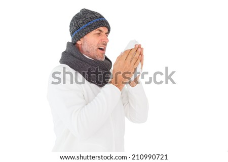 Sick man in winter fashion sneezing on white background