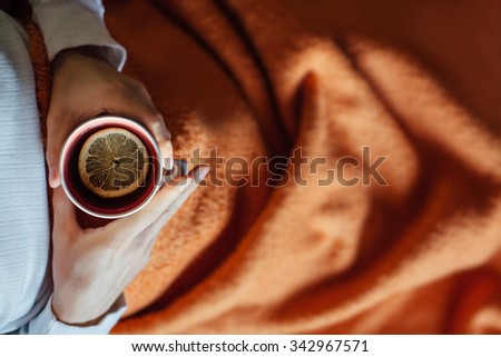 Sick man laying in bed under blanket and holding cup of tea with lemon. Copy space on orange blanket. - stock photo