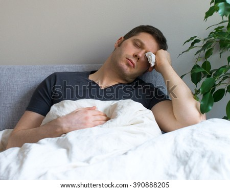 Sick man lying in the bed with fever. - stock photo