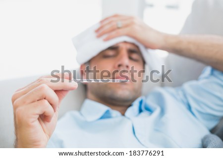 Sick man lying on sofa checking his temperature at home in the living room - stock photo