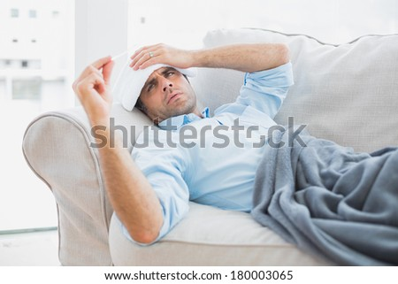 Sick man lying on sofa checking his temperature under a blanket at home in the living room - stock photo