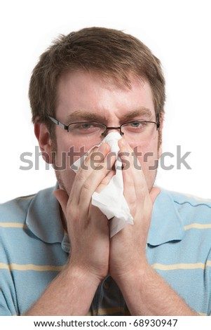 Sick man with a cold blowing nose on tissue - stock photo