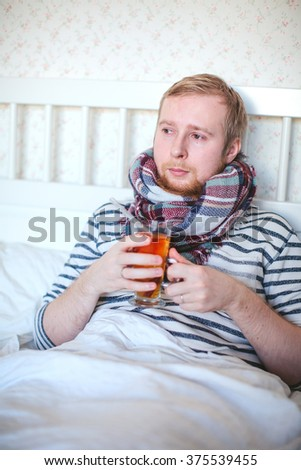 sick man with a thermometer and hot tea lying in bed - stock photo