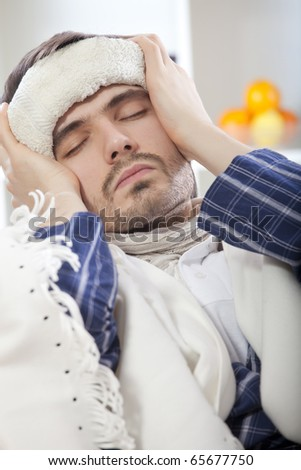 sick man with high fever lying in bed with wet towel on his forehead - stock photo