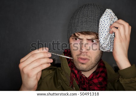 Sick man with thermometer and ice pack on head - stock photo