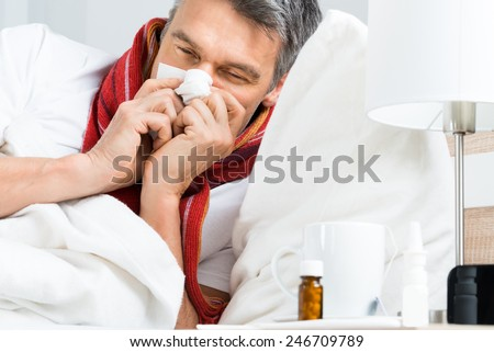 Sick Mature Man Blowing His Nose While Lying On Bed At Home - stock photo