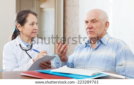sick mature man complaining  to doctor about symptoms of malaise near table with documents