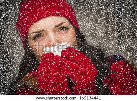Sick Mixed Race Woman Wearing Winter Hat and Gloves Blowing Her Sore Nose with a Tissue in The Snow. - stock photo