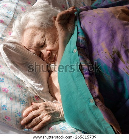 Sick old woman lying in bed