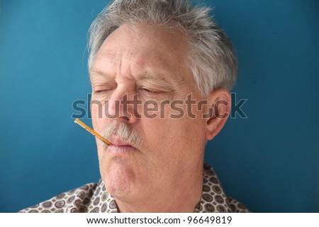 sick older man checks his temperature - stock photo