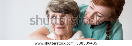 Sick older smiling woman and her young caregiver