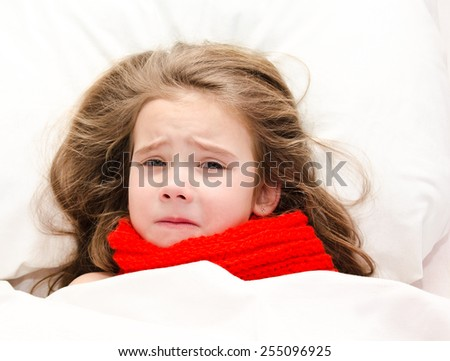 Sick sad little girl lying in the bed in red scarf - stock photo