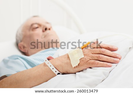 Sick senior lying in a hospital bed with iv drip attached on his hand with the focus on the iv set isolated on white background - stock photo
