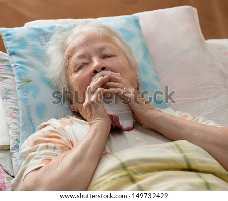 Sick senior woman lying at bed - stock photo