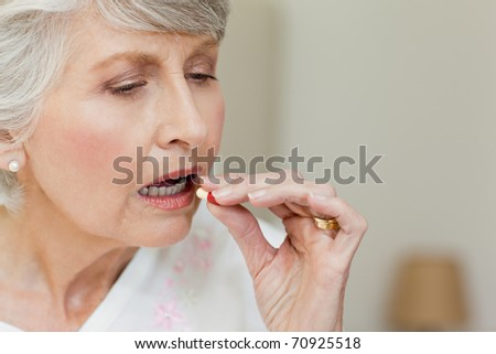 Sick senior woman taking her pills at home