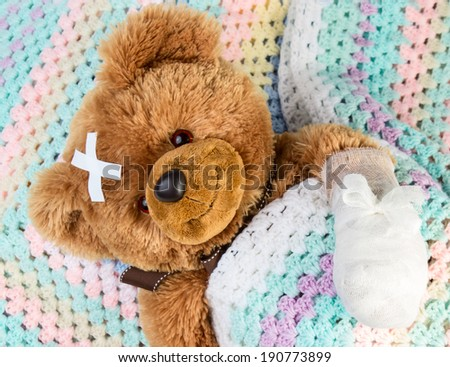 Sick teddy bear with bandage in a bed - stock photo