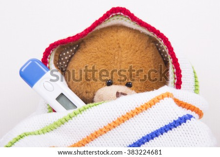sick teddy bear with thermometer