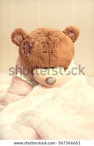 Sick teddy bear with thermometer in bed - stock photo