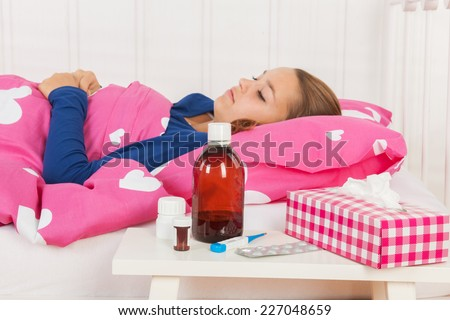 Sick teen girl laying in bed with medicine in front (focus on medicine) - stock photo