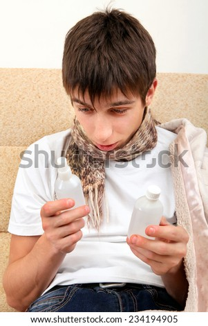 Sick Teenager choice the Medicine on the Sofa at the Home - stock photo