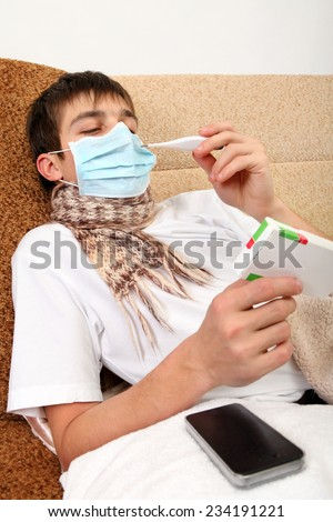 Sick Teenager in Flu Mask with pack of pills on the Sofa at the Home - stock photo