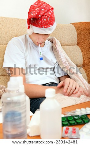 Sick Teenager in Santa Hat with Thermometer on the Sofa with the Pills on the Table - stock photo
