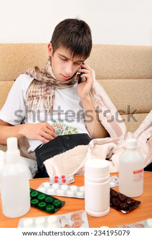Sick Teenager with Cellphone checking the Wallet on the Sofa at the Home - stock photo