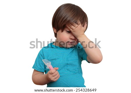 Sick toddler boy holding medicine on white. Ill little child taking antibiotic, holding his hand to his head, looking sad. Horizontal image of toddler who is not feeling well and has a fever.