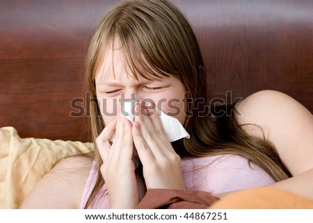 Sick with flu teenager girl in bed sneezing - stock photo