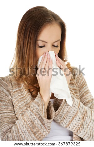 Sick woman blowing her nose.