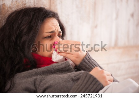 Sick woman caught a cold. Closeup image of frustrated young woman with red nose lying in bed with thick scarf and sneezing into tissue - stock photo