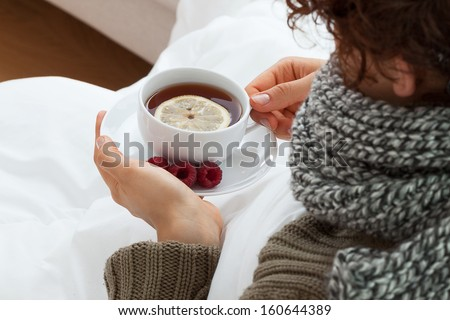 Sick woman drinking hot tea with lemon and raspberries - stock photo