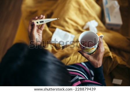 Sick woman drinking tea holding thermometer on couch - stock photo