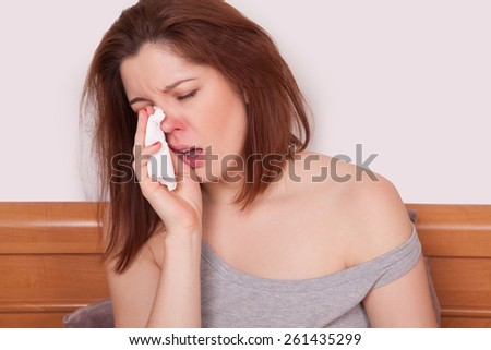 Sick Woman. Flu. Woman Caught Cold. Sneezing into Tissue. Headache. Virus. copy space - stock photo