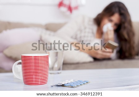 Sick Woman, Flu Woman. Caught Cold. Woman with headache typing on cell phone, shallow depth of field - stock photo