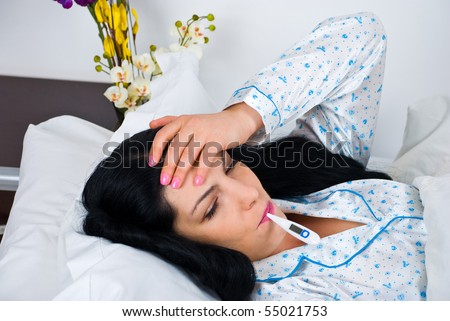Sick woman having cold and fever and lying on bed checking temperature and holding hand on forehead - stock photo